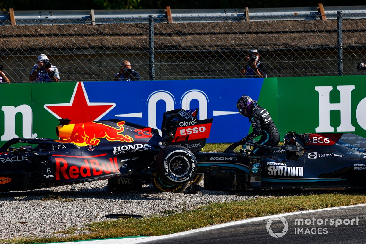 Lewis Hamilton, Mercedes, climbs out of his car after crashing out with Max Verstappen, Red Bull Racing RB16B