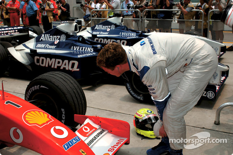 Ralf Schumacher inspecting the tires on the Ferrari