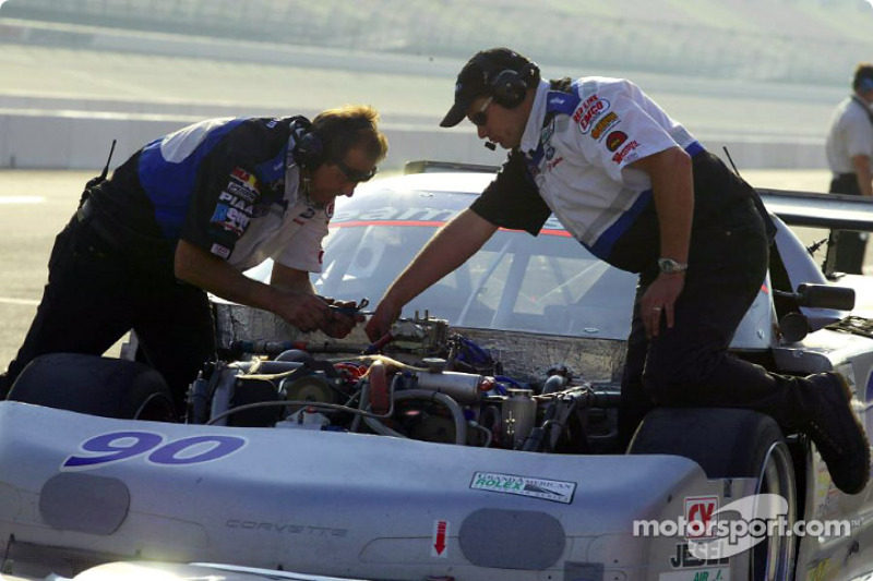 The crew of the #90 Flis Motorsports Corvette works in the pits during a practice session
