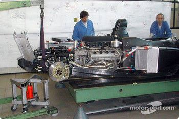 Technicians at the Dallara Automobili factory in Parma, Italy, install the Infiniti Q45 engine/transmission assembly to the Pro Series chassis