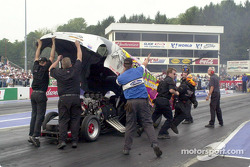 Todd Paton scrambles from the car after it stalls on the track