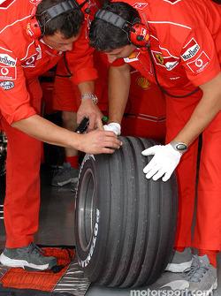 Ferrari crew members prepare the tires
