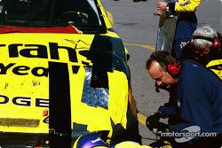 Crew repair damage on Larry Foyt's car