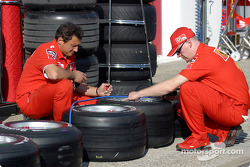 Ferrari team members prepare the tires