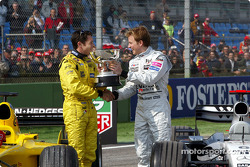 Giancarlo Fisichella receives the winner's trophy for the Brazilian GP from Kimi Raikkonen