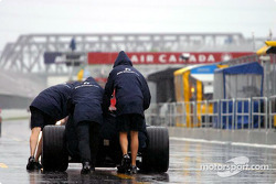 Williams team members push the car on pitlane