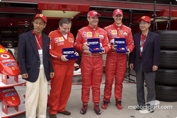 Jean Todt, Rubens Barrichello and Michael Schumacher receives a gift from Olympus