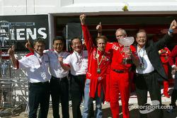 Luca Badoer, Rory Byrne and Bridgestone team members celebrate victory