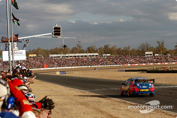 Marcos Ambrose takes the chequered flag