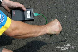 Renault F1 team member checks track temperature