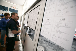 Team members look at the list of drivers on the notice board who were given time penalties following the Friday practice session