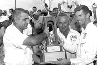 Ray Nichels and Paul Goldsmith are accepting the First Place trophy for winning the 150-mile USAC race