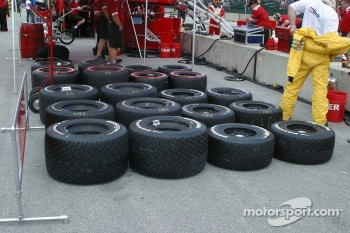 A wide variety of tires sit behind the wall