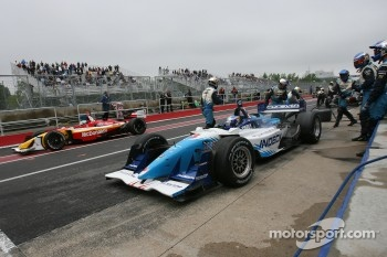 Paul Tracy exits his pit while Sbastien Bourdais passes by