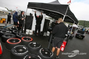 Teams set up tents in pit area as the rain drops on and off