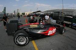 Minardi Team USA crew members take Robert Doornbos' car back to paddock
