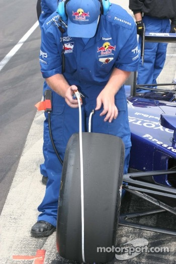 A crew member checks the circumference of a tire