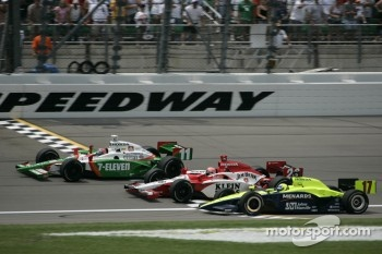 Tony Kanaan takes the checkered flag ahead of Dan Wheldon and Vitor Meira