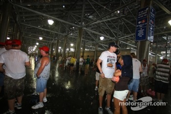 Fans try to stay dry by camping out underneath the grandstands