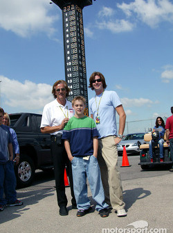 Arie Luyendyk and Arie Luyendyk Jr. with a young fan
