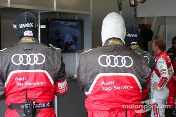 Allan McNish and the Audi team members watch the F1 Practice