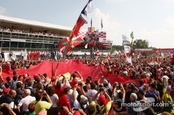 Fans on the track enjoy the podium