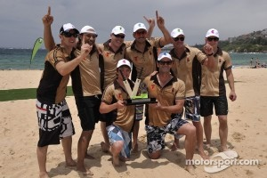 The team of New Zealand V8 Supercar drivers and celebrities pose with the trophy after they beat a team of their Australian counterparts in a beach cricket match