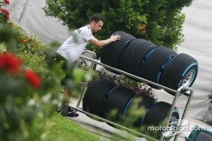 A Mercedes GP mechanic wheels wet Pirelli tyres through the paddock