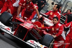 Ferrari F2012 pushed to scrutineering by mechanics