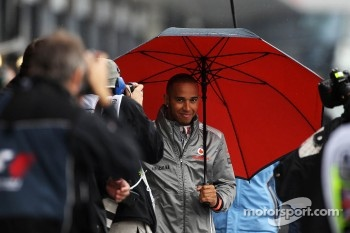 Lewis Hamilton, McLaren walks through the pits with an umbrella