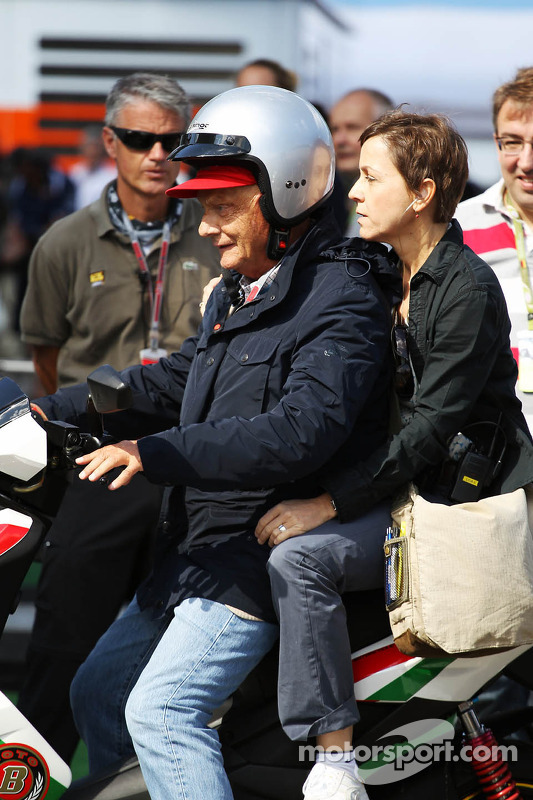 Niki Lauda, arrrives at the circuit on a motorbike