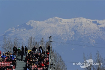 Fans in the grandstand with snow on the mountains