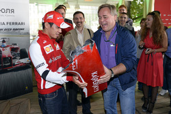 Kamui Kobayashi presents Eugene Kaserspky with a piece of his wrecked Ferrari F1