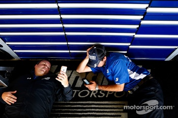 Hendrick Motorsports crew members wait for the rain to stop