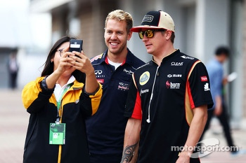 (L to R): Sebastian Vettel, Red Bull Racing and Kimi Raikkonen, Lotus F1 Team pose for a photo with a fan in the paddock