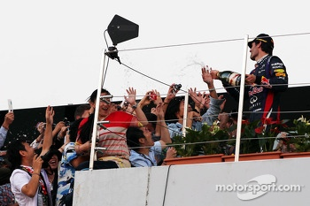 Mark Webber, Red Bull Racing celebrates his second position with the champagne with fans on the podium