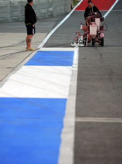 Workers paint pitlane