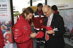Jarno Trulli signs a Red Cross cap