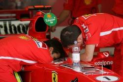 Ferrari team members refill the water tank