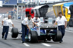 Sauber team members push the car back to the garage