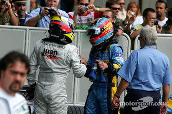 Race winner Juan Pablo Montoya celebrates with Fernando Alonso