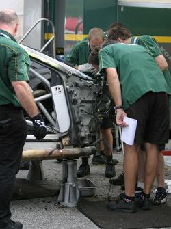 Aston Martin Racing crew members work on the wrecked #58 Aston Martin DB9