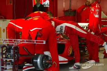 Michael Schumacher and Ferrari team members inspect the Ferrari