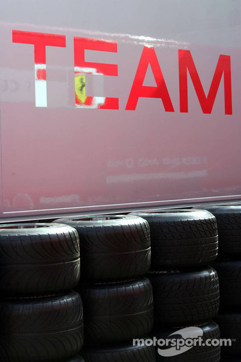 Reflection of a Ferrari transporter in a McLaren Mercedes transporter