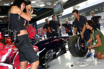 Formula Unas girl Claudia Cimini with Scuderia Toro Rosso crew members and a photographer