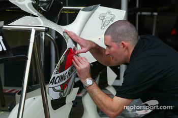 Honda Racing team member prepares the cars stickers for the last race in F1 for Lucky Strike
