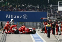Michael Schumacher is pushed back into the garage after a problem