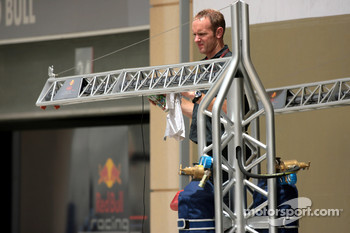 A Red Bull Racing crew member cleans the gibbet