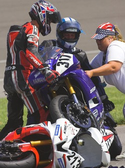 Corner worker helps David Anthony and Mike Shreve separate their mangled Yamahas