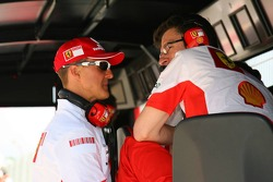 Michael Schumacher, Scuderia Ferrari, Advisor talks with Chris Dyer, Scuderia Ferrari, Track Engineer of Kimi Raikkonen on the pit wall